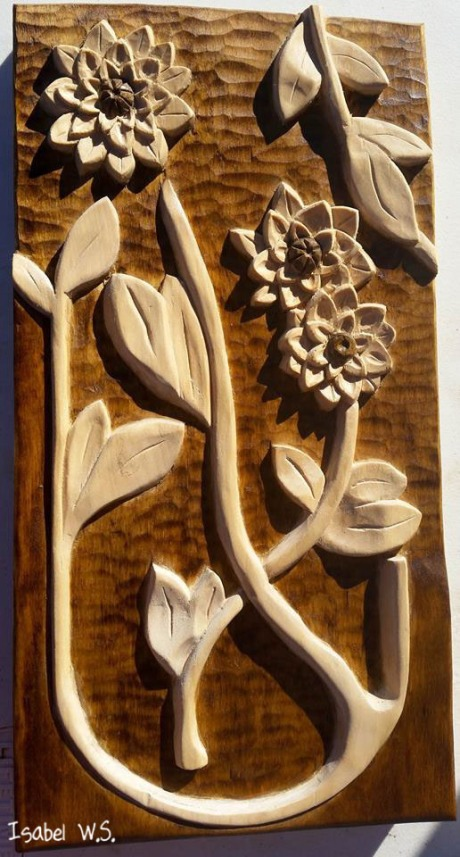 3 dahlia flowers, relief woodcarving, on a dark background