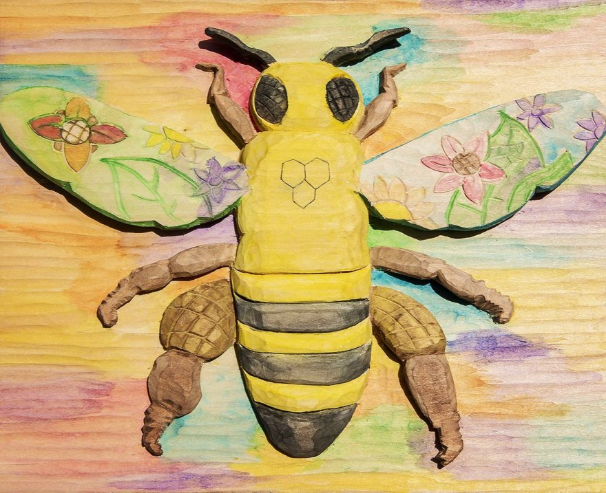 A dimensional bee woodcarving done in rainbow watercolors