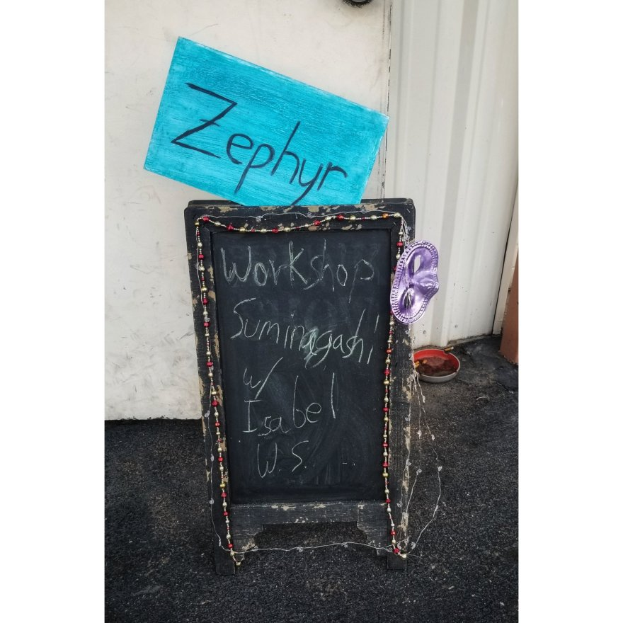 A sign with purple Mardi Gras mask, chalk writing, and Christmas lights. The sign says