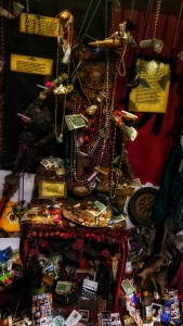 Altar at the Vodoo Musuem in New Orleans, lots of mardi gras beads, photographs, and money. Text cards explain the different Orisha.