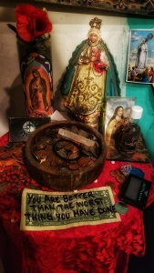 "Altar at the Voodoo Museum, featuring 4 depictions of Mother Mary and a dolalr bill that says,""You are better than the worst thing you have done."""