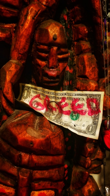 A red, carved face, and a dollar bill that says GREED in red