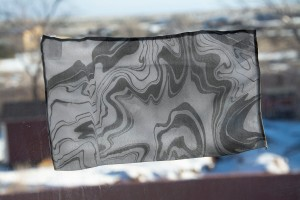 silk fragments taped to a window, each with a unique suminagashi pattern