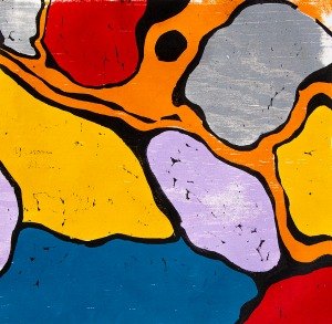 brightly colored jigsaw print, reds, light violet, yellow, blue, & gray